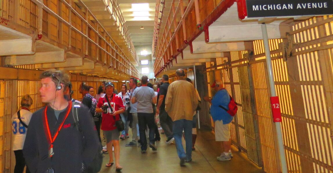 visit_alcatraz_prison_cell_block_tourists_walking_by_inmates_cells_