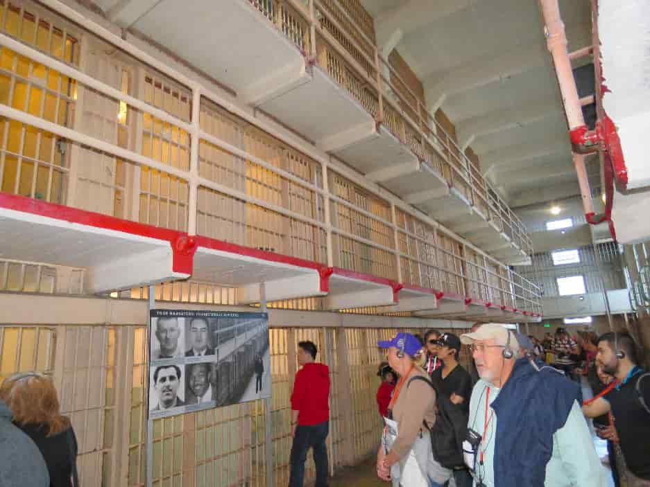 visitors-walking-tour-inside-Alcatraz-Penitentiary-cell-block-min-